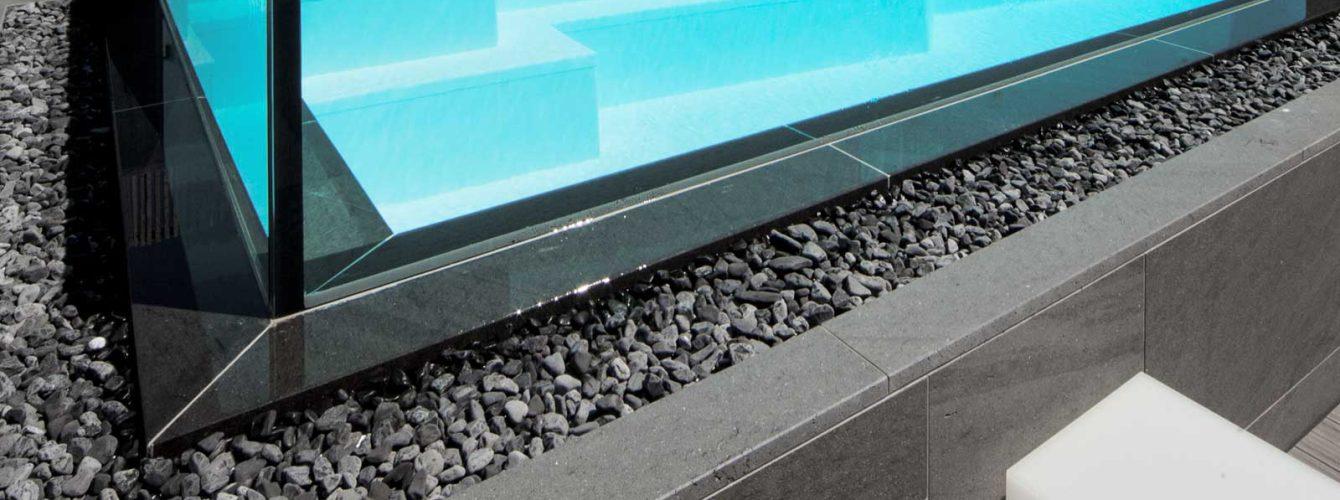 piscina con lati a cascata che fanno scorrere l'acqua sul canale con ciottoli