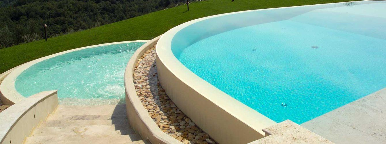 piscina a forma libera con sfioro cascata e ciottoli levigati
