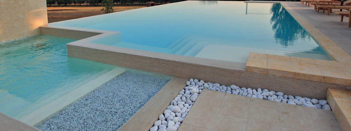 piscina color sabbia a sfioro e ciottoli