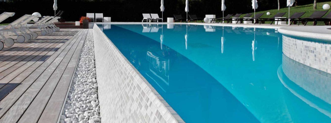 piscina con lato cascata e ciottoli