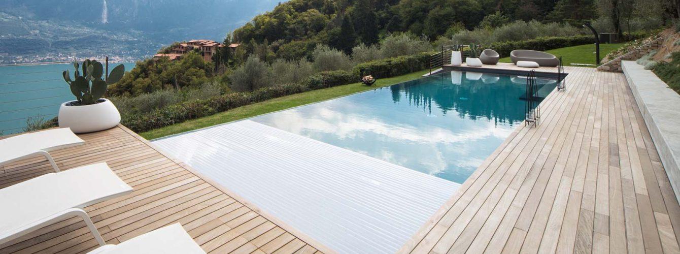 piscina con telo grigio e copertura a tapparella, sfioro cascata