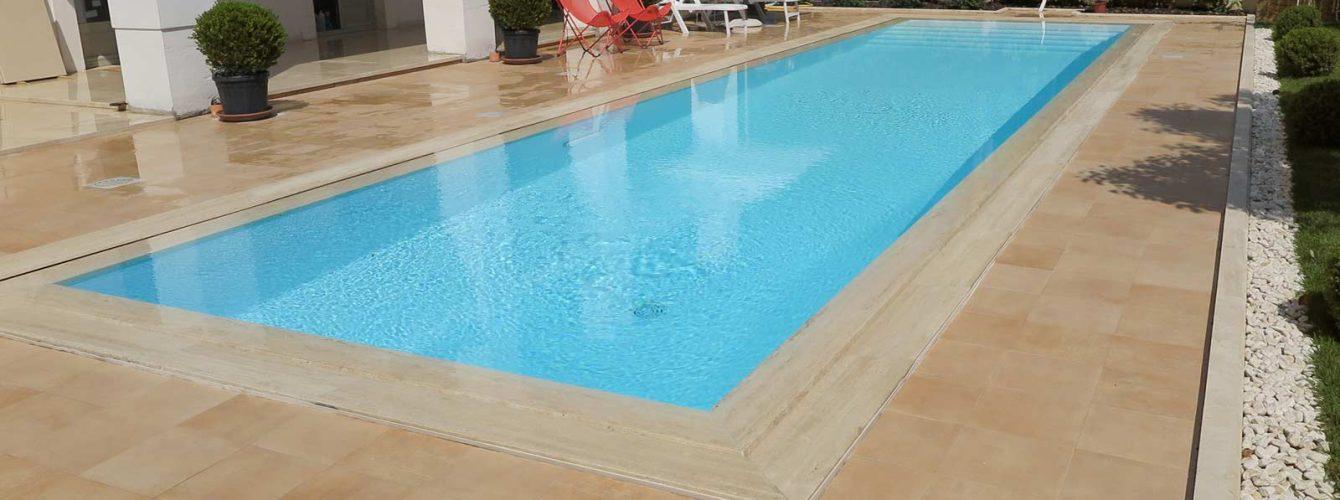 piscina rettangolare con sfioro trilogy, rivestimento bianco e finiture marmo-cemento