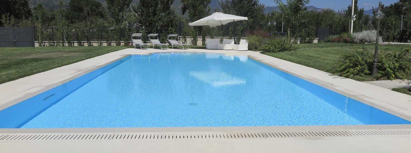 piscina con scala romana bianca, a sfioro con griglia in pietra