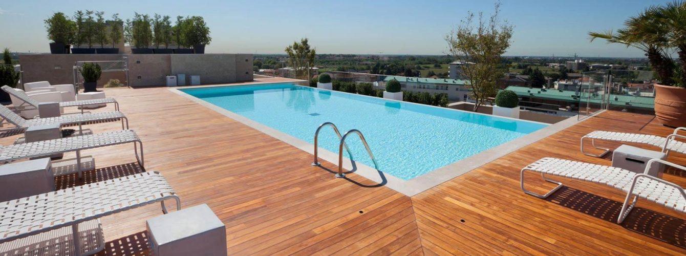 piscina azzurra rettangolare con cascata e scaletta