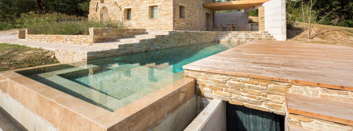 piscina rettangolare seminterrata con cascata e area idromassaggio