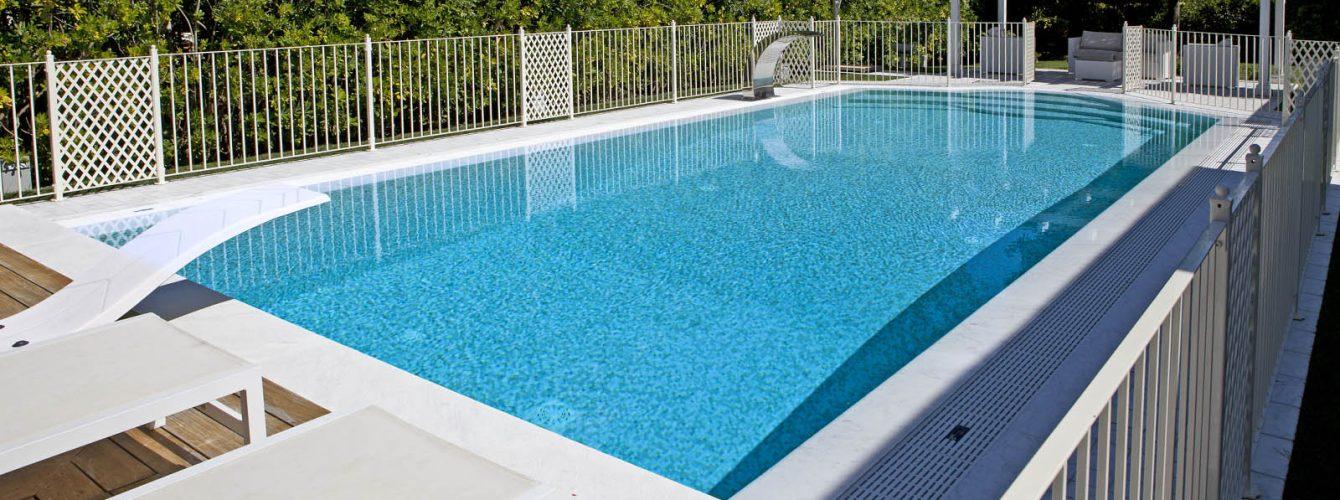 piscina bordo sfioro rettangolare in mosaico con cascata e trampolino