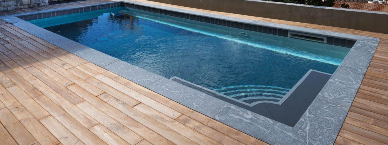 piscina skimmer rettangolare con rivestimento nero, solarium in legno