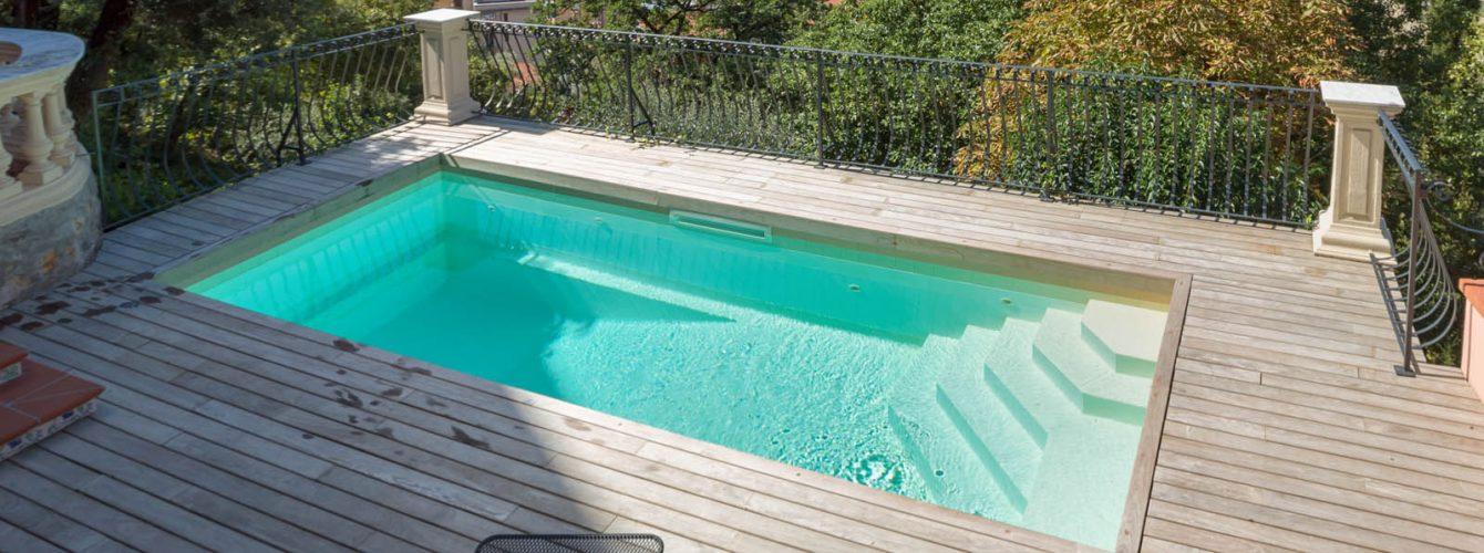 piscina skimmer rettangolare bianca con scala ad angolo, con rivestimento esterno in legno