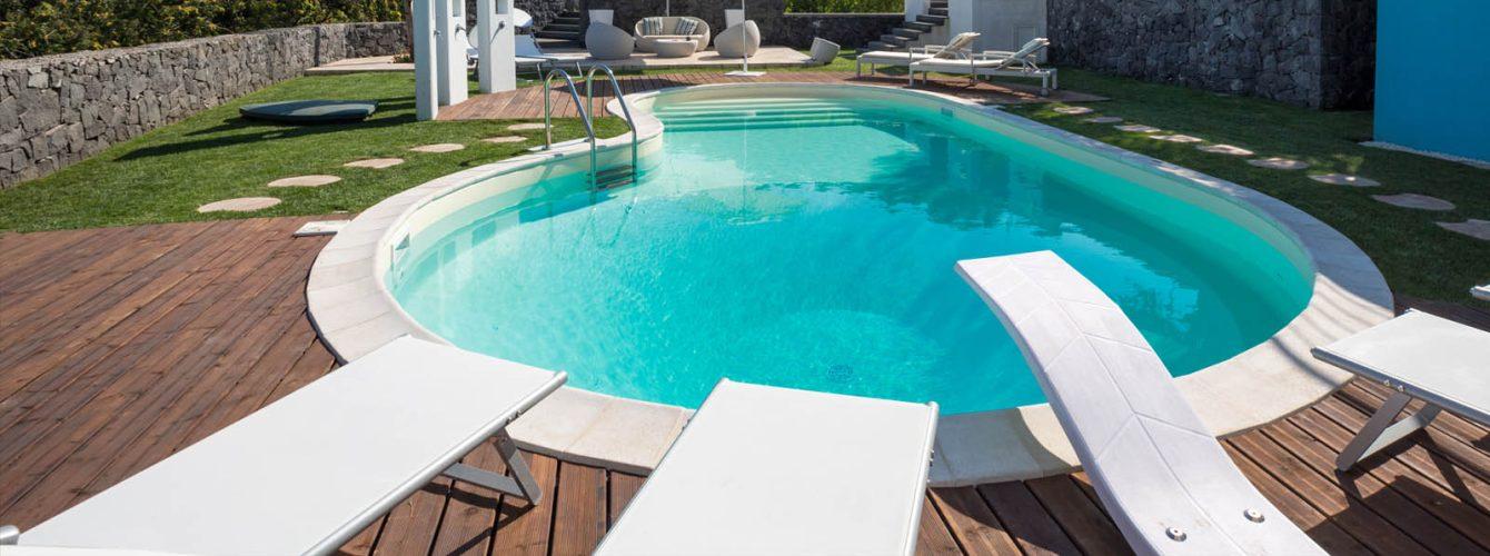 piscina a forma libera, color sabbia con trampolino e scalinata d'ingresso