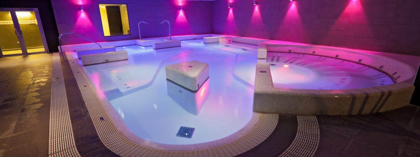 piscina idromassaggio a forma libera, con luci e mosaico