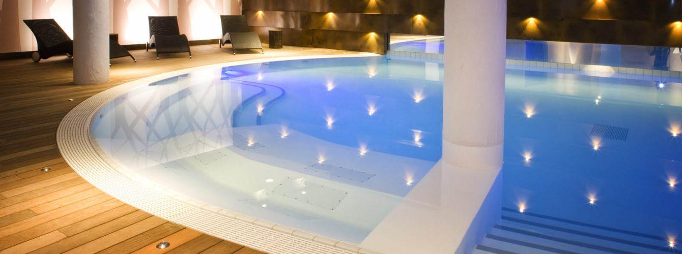 piscina a forma libera con panche idromassaggio e scale