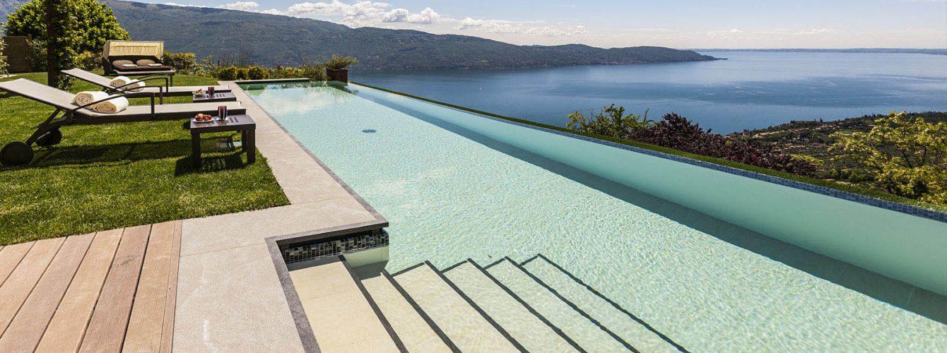 piscina rettangolare vista lago con cascata e scale