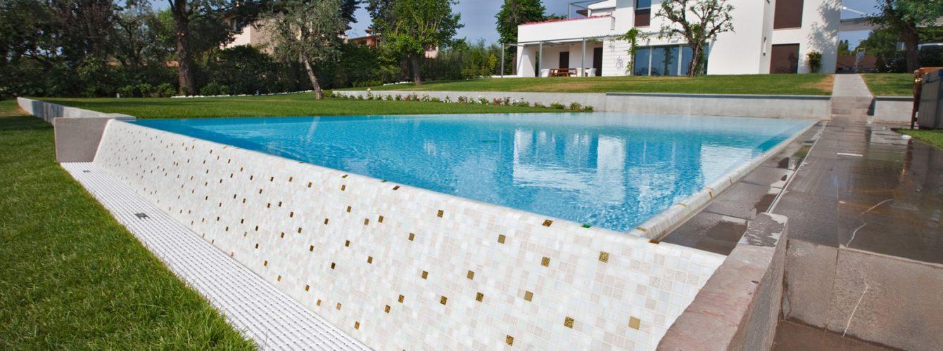 piscina rettangolare con cascata, scala, rivestimento bianco e mosaico