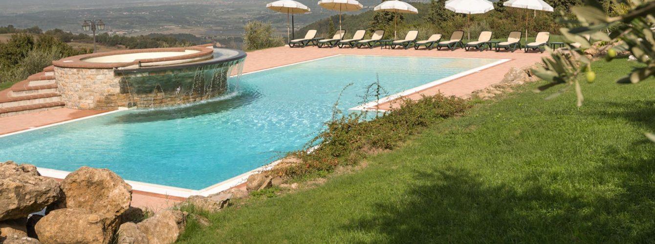 piscina rettangolare con idromassaggio, cascata e scalinata