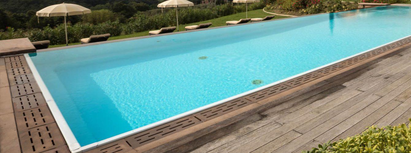 piscina rettangolare a sfioro color sabbia, esterno in legno