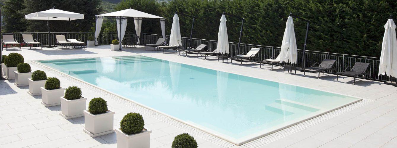 piscina rettangolare a bordo sfioro con scale e panche idromassaggio