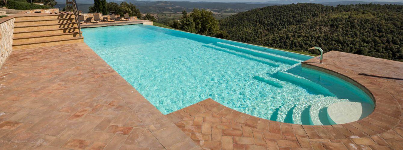 piscina rettangolare color sabbia con scala romana d'ingresso e panca con idromassaggi