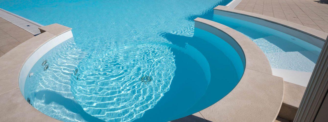 piscina bianca a sfioro con area idromassaggi e scalinata