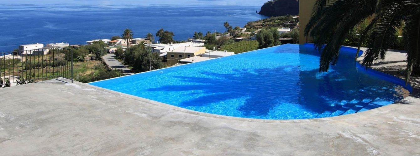 piscina azzurra a forma libera con cascata e scalinata