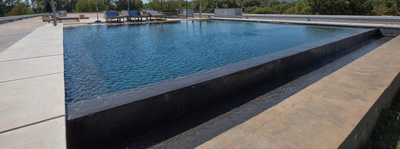 piscina nera esterna riscaldata con cascata e bordo sfioro