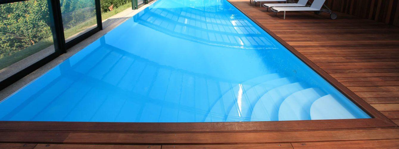 piscina interna con cascata e scala ad angolo, pavimentazione del solarium e copertura automatica rivestita in legno