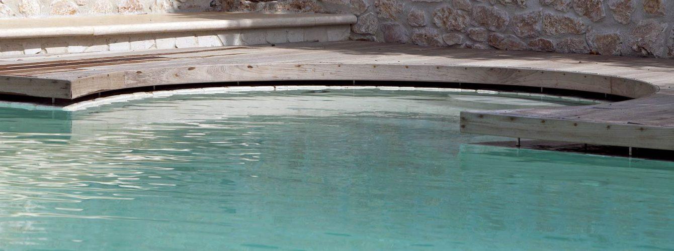 particolare di un'area relax in piscina con sfioro nascosto al di sotto del pavimento
