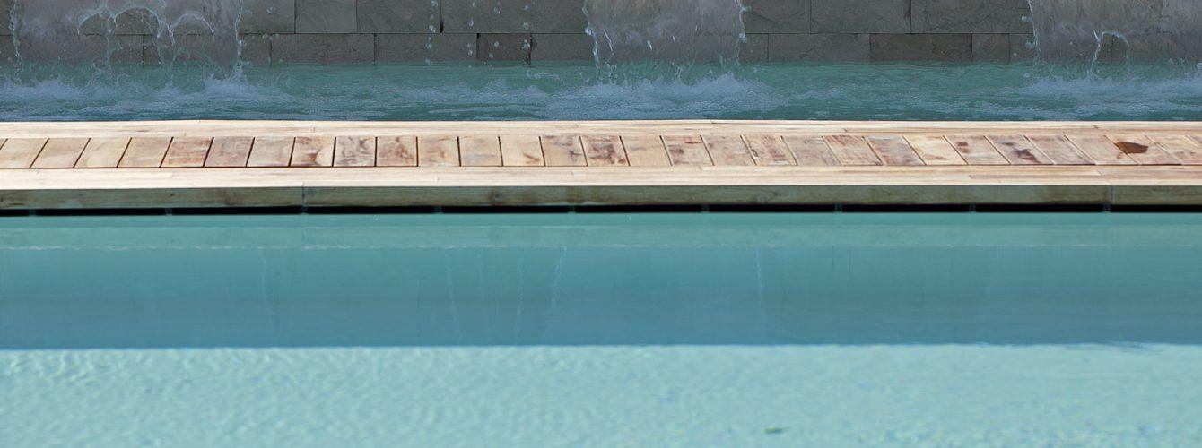 particolare di piscina con cascate e passatoia in legno al di sotto della quale l'acqua scorre grazie allo sfioro nascosto