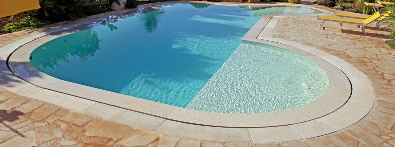 piscina a forma libera color sabbia con bordo sfioro, zona relax e scalinata d'ingresso