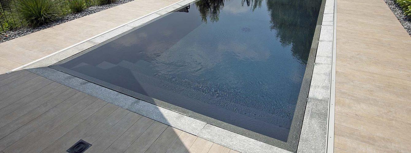 piscina grigia a sfioro con materiali pregiati e sistema trilogy