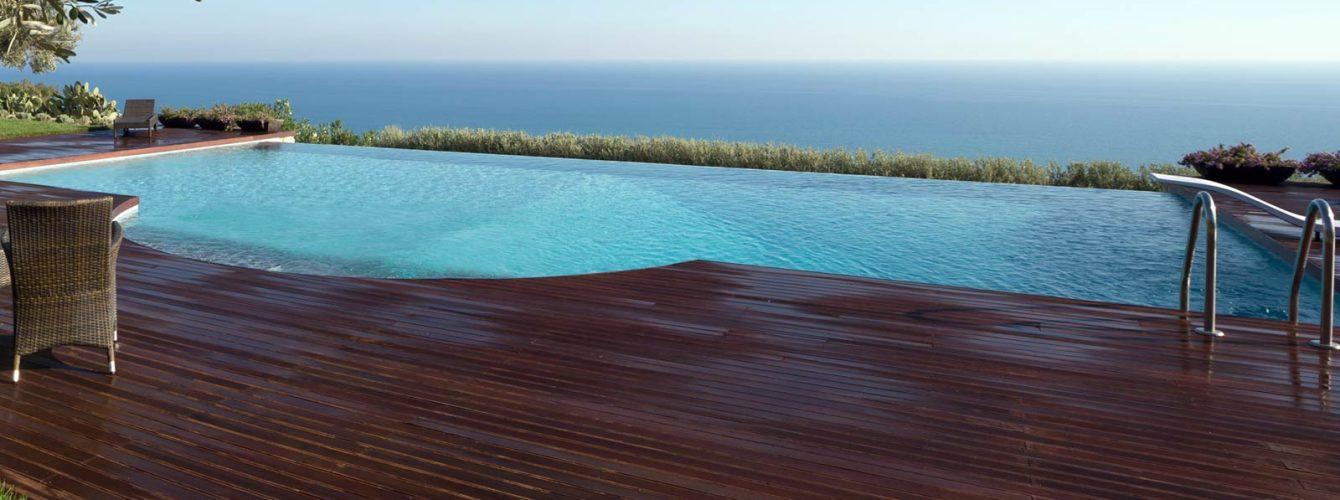 piscina grigia a cascata con scala romana e trampolino, solarium in legno scuro