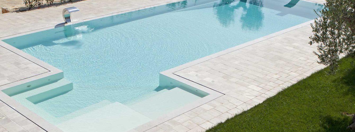 piscina a sfioro color sabbia, con trampolino e area idromassaggio