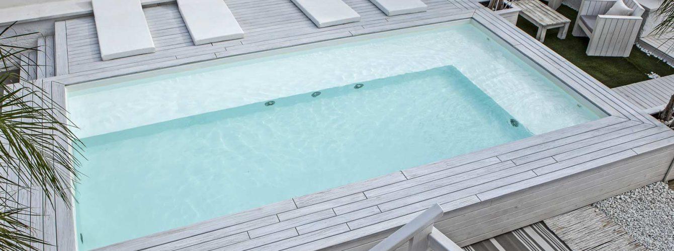 piscina fuoriterra con solarium in legno, idromassaggio con panca e fari, rivestimento bianco,