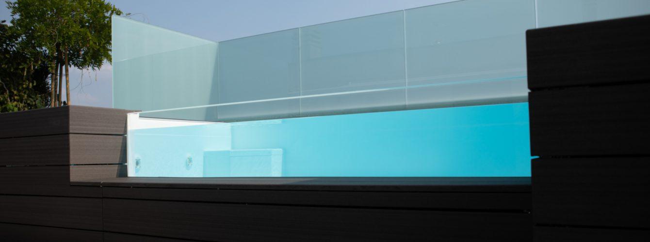 Piscina su terrazzo con parete in cristallo