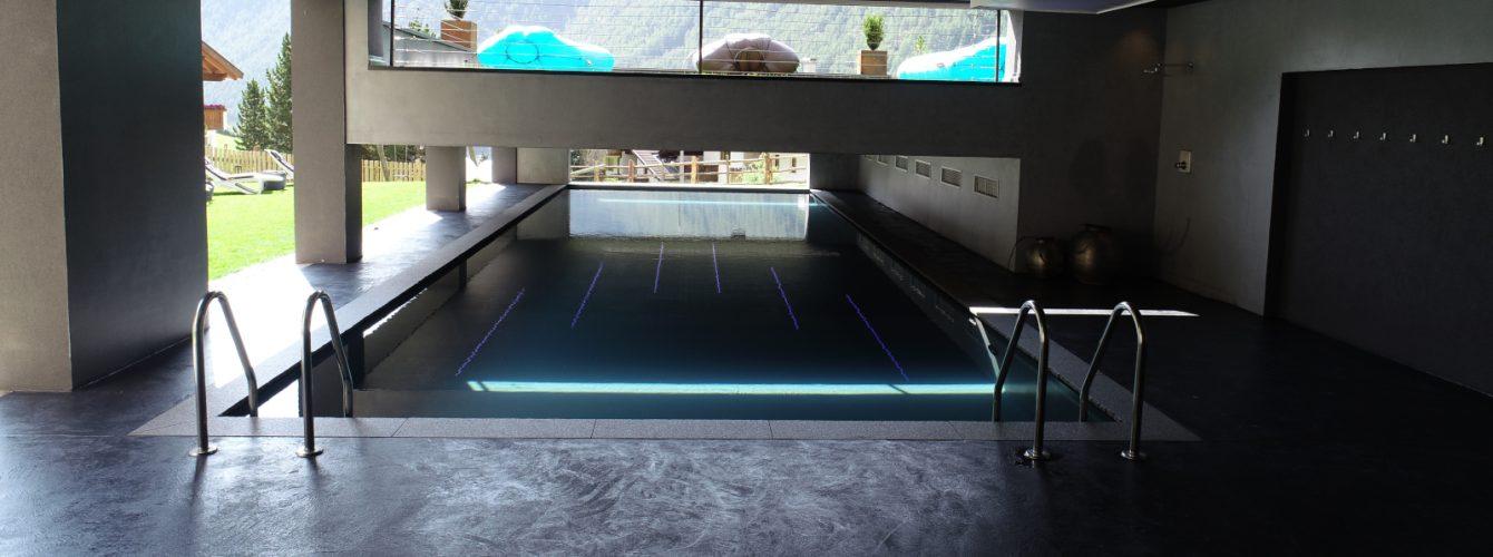 Piscina rettangolare semicoperta con luci sul soffitto