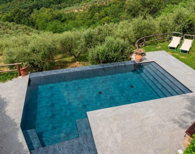 piscina con forma personalizzata grigia, con lato a cascata e scalinata di ingresso