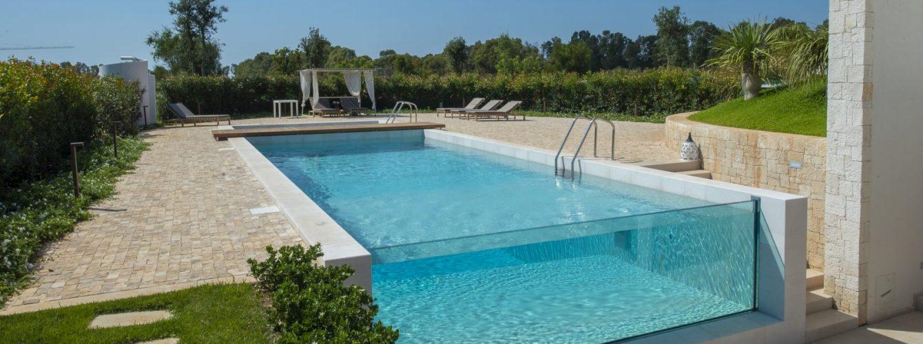 piscina rettangolare seminterrata a skimmer con parete in vetro metacrilato