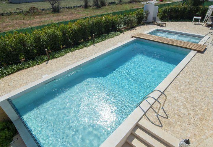piscina rettangolare seminterrata con zona idromassaggio e parte in vetro metacrilato