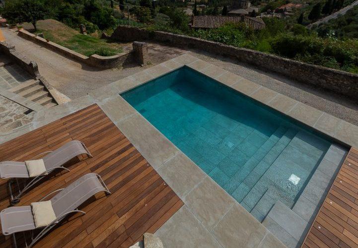 piscina per famiglia, seminterrata a sfioro nascosto con scala d'ingresso, rivestita in gres