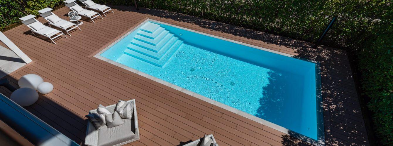 Piccola piscina con sfioro trilogy e bordo in pietra, scala d'ingresso, illuminazione