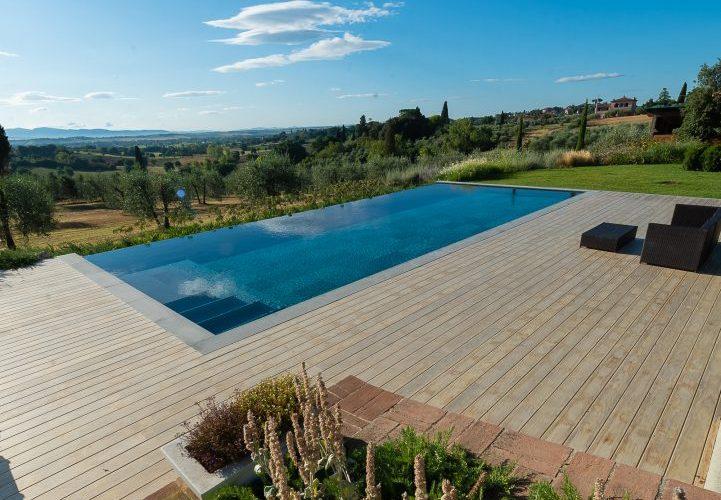 piscina nera con lato a cascata e scala di ingresso