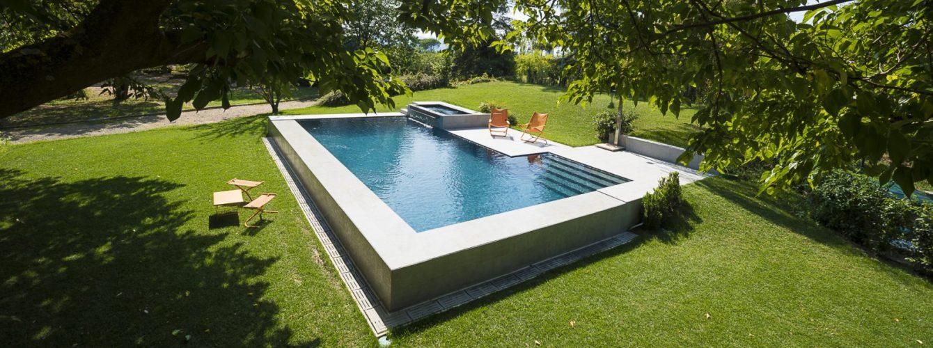 piscina seminterrata rivestita in pvc grigio con scale e vasca idromassaggio