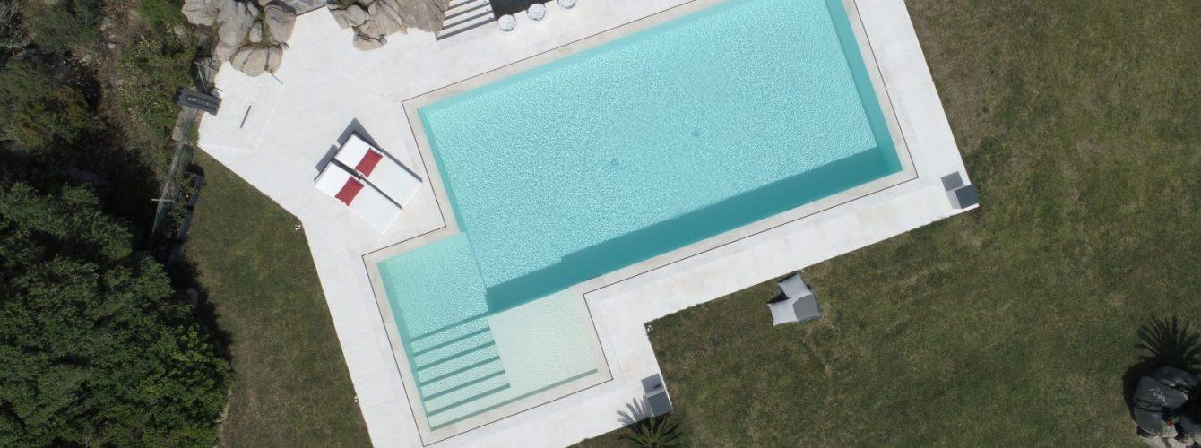 piscina rettangolare con appendice per scale e spiaggetta, a sfioro, vista dall'alto