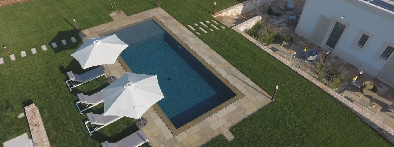 piscina rettangolare grigia con sfioro trilogy e spiaggetta