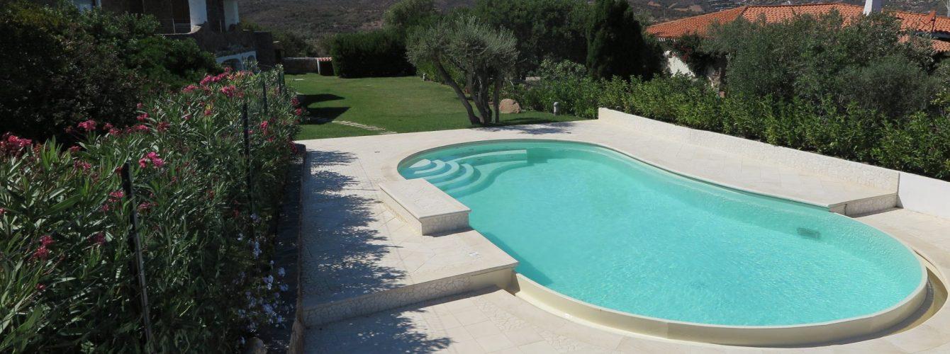 piscina a forma libera color sabbia con cascata e scale di ingresso