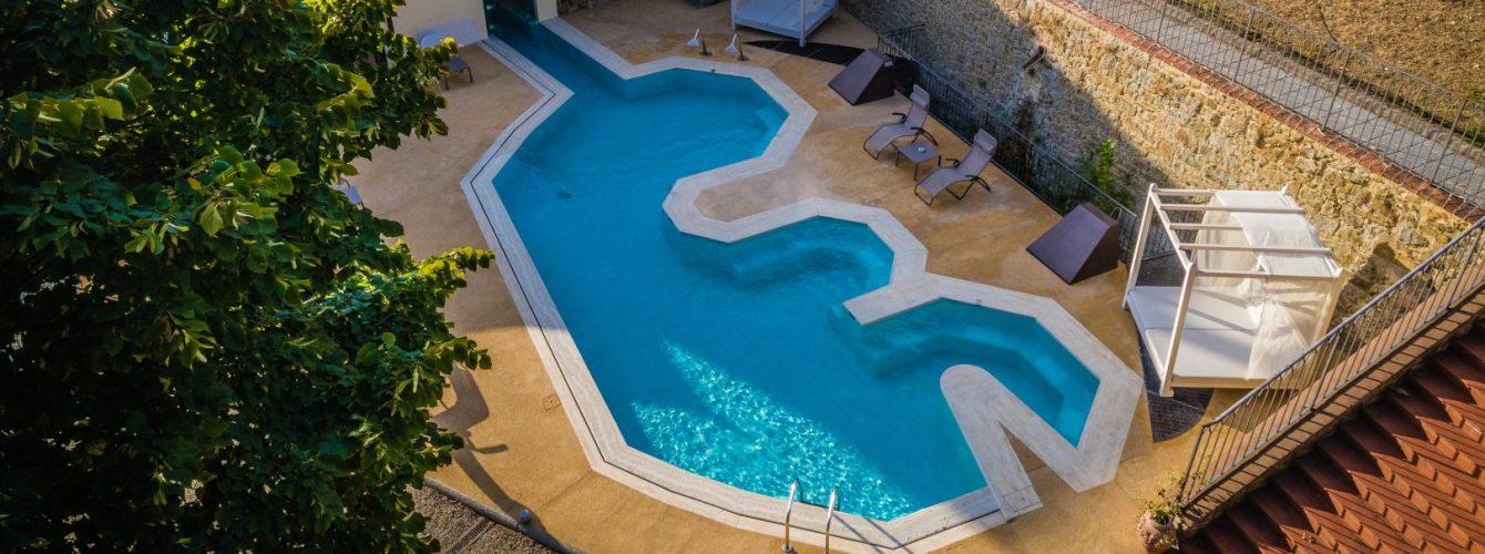 piscina a forma libera per hotel con panche e zone idromassaggio collegata con piccola piscina interna