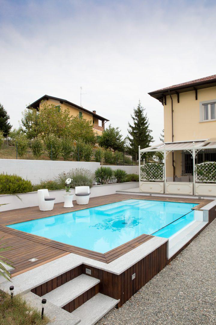 piscina fuoriterra a sfioro con parete crystal e scale di ingresso