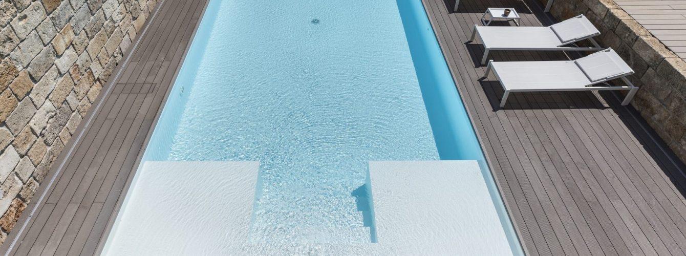 piscina rettangolare bianca con sfioro nascosto, scale e spiaggette