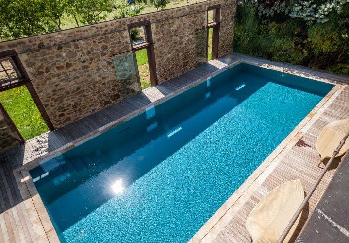 piscina in stalla riconvertita con parete di verde verticale, piscina a sfioro